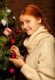 La muchacha adorna el árbol de navidad Fotografía de archivo
