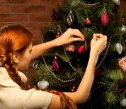 La muchacha adorna el árbol de navidad Imagenes de archivo