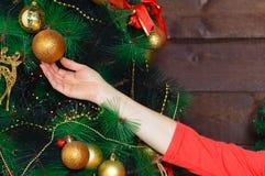 La muchacha adorna el abeto de la Navidad imagen de archivo