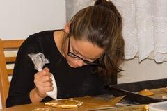 La muchacha adorna el pan de jengibre con la crema blanca en la tabla Fotos de archivo libres de regalías
