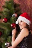 La muchacha adorna el ?rbol de navidad Fotos de archivo