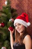 La muchacha adorna el ?rbol de navidad Imagenes de archivo