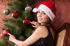 La muchacha adorna el ?rbol de navidad Foto de archivo libre de regalías