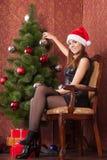 La muchacha adorna el ?rbol de navidad Imagen de archivo libre de regalías