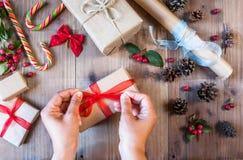 La muchacha adorna el regalo de la Navidad, ata el arco rojo Fotografía de archivo