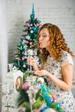 La muchacha adorna la casa para la Navidad Imágenes de archivo libres de regalías