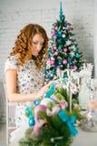La muchacha adorna la casa para la Navidad Foto de archivo libre de regalías