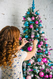 La muchacha adorna la casa para la Navidad Imagenes de archivo