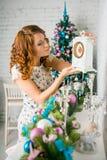 La muchacha adorna la casa para la Navidad Fotos de archivo libres de regalías