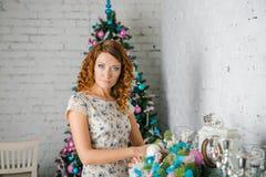 La muchacha adorna la casa para la Navidad Imagen de archivo
