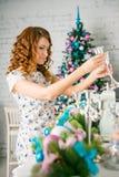 La muchacha adorna la casa para la Navidad Fotografía de archivo