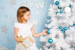 La muchacha adorna las bolas y la sonrisa del árbol de navidad Imágenes de archivo libres de regalías