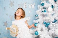 La muchacha adorna las bolas y la sonrisa del árbol de navidad Foto de archivo libre de regalías