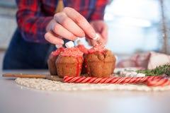 La muchacha adorna las magdalenas de la celebración del Año Nuevo, molletes del chocolate en la tabla imagenes de archivo