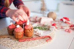 La muchacha adorna las magdalenas de la celebración, molletes del chocolate en la tabla fotos de archivo libres de regalías
