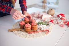 La muchacha adorna las magdalenas de la celebración, molletes del chocolate en la tabla fotografía de archivo