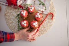 La muchacha adorna las magdalenas de la celebración del Año Nuevo Imágenes de archivo libres de regalías