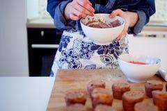 La muchacha adorna las magdalenas, sosteniendo la placa, los molletes y la placa de los ingredientes para la decoración en la tab Fotografía de archivo libre de regalías