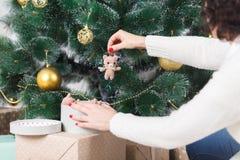 La muchacha adorna un árbol de navidad Imagen de archivo