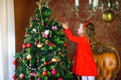 La muchacha adorna un árbol de navidad festivo Imagen de archivo