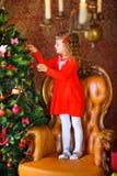 La muchacha adorna un árbol de navidad festivo Fotografía de archivo libre de regalías
