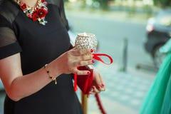 La muchacha adornada con una palmatoria decorativa en sus manos y una muestra lleva a cabo una vela en su mano en el fondo fuera foto de archivo