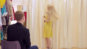 La muchacha adulta atractiva con sonrisa muestra el vestido amarillo al individuo en vestuario
