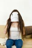 La muchacha adulta cubre su cara con sonrisa triste dibujada en el papel con uno Imagen de archivo libre de regalías