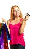 La muchacha adulta joven del retrato con los bolsos coloreados sostiene la tarjeta de crédito Imágenes de archivo libres de regalías