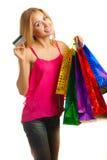 La muchacha adulta joven del retrato con los bolsos coloreados sostiene la tarjeta de crédito Imagen de archivo libre de regalías