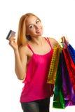 La muchacha adulta joven del retrato con los bolsos coloreados sostiene la tarjeta de crédito Imagenes de archivo