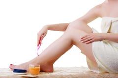 La muchacha afeita sus piernas agradables Imagen de archivo libre de regalías