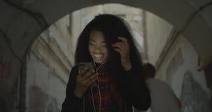 La muchacha africana atractiva feliz está bailando mientras que escucha la música vía los auriculares en la calle cantidad 4k almacen de video