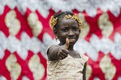 La muchacha africana joven con los accesorios tradicionales en el pelo que muestra los pulgares sube la muestra y la mirada de la Imagen de archivo libre de regalías