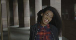 La muchacha africana sonriente alegre alegre está caminando abajo de las escaleras hacia la cámara cantidad 4k Retrato al aire li metrajes