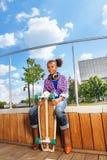 La muchacha africana sostiene el monopatín y sentarse en lado Foto de archivo libre de regalías