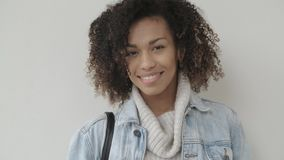 La muchacha afroamericana en ropa casual est? mirando la c?mara y la sonrisa metrajes