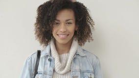 La muchacha afroamericana en ropa casual est? mirando la c?mara y la sonrisa almacen de video