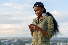 La muchacha afroamericana encantadora escucha la música y la relajación Señora negra joven sonriente en fondo borroso de la ciuda Imagen de archivo libre de regalías