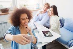 La muchacha afroamericana está tomando un selfie de sí misma y sus amigos que se están sentando en la tabla Todos están presentan Fotografía de archivo libre de regalías