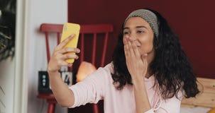 La muchacha afroamericana feliz está haciendo la llamada video con smartphone amarillo que llama a los amigos que hablan la senta metrajes