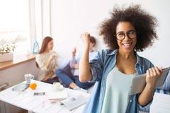 La muchacha afroamericana se está colocando delante de cámara y de la sonrisa Ella celebra una tableta y señalar en sus amigos qu Fotos de archivo