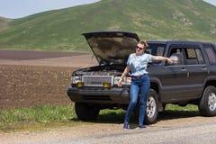 La muchacha agita abajo del coche Fotos de archivo libres de regalías
