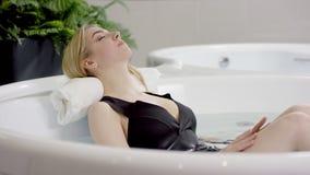 La muchacha agradable con el busto emocionante goza el relajarse en un Jacuzzi caliente con su cabeza en la toalla contra la otra almacen de video