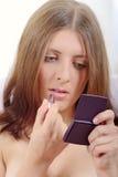 La muchacha agradable con el lápiz labial y un espejo Foto de archivo
