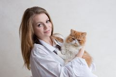 La muchacha agradable con un gato rojo en las manos Fotos de archivo
