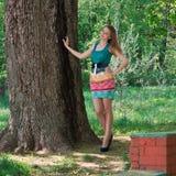 La muchacha agradable delgada joven en una sombra del árbol Imagen de archivo