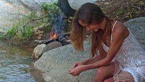 La muchacha agradable en el vestido blanco se sienta en Rocky River Bank por el fuego metrajes