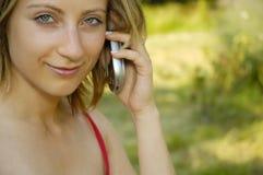 La muchacha agradable en hierba-traza con el teléfono celular Fotografía de archivo