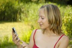 La muchacha agradable en hierba-traza con el teléfono celular Fotos de archivo libres de regalías